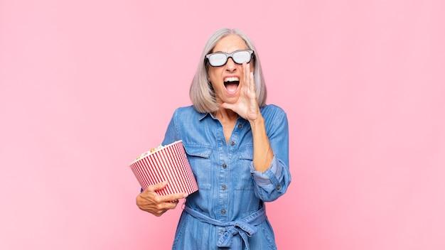 Frau mittleren alters, die sich glücklich, aufgeregt und positiv fühlt und mit den händen neben dem mund einen großen schrei ausstößt