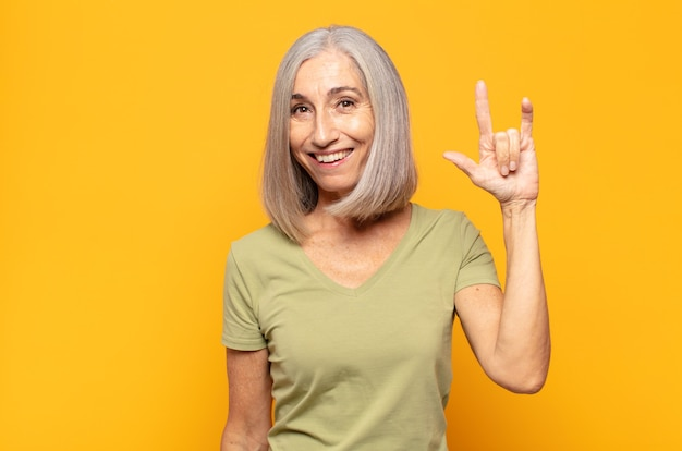 Frau mittleren alters, die sich glücklich, lustig, selbstbewusst, positiv und rebellisch fühlt und mit der hand rock- oder heavy-metal-zeichen macht