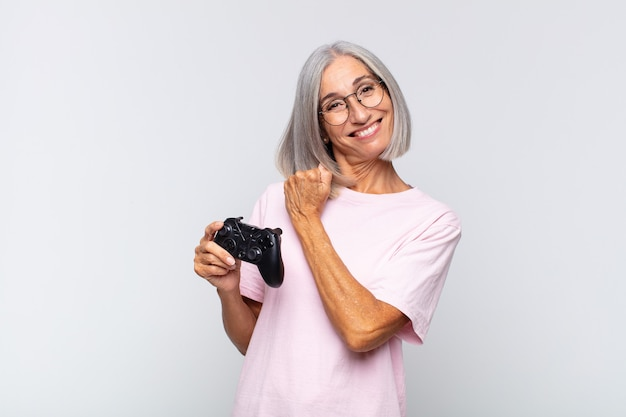Frau mittleren alters, die sich glücklich positiv und erfolgreich motiviert fühlt, wenn sie sich einer herausforderung stellt oder gute ergebnisse beim spielen des konsolenkonzepts feiert