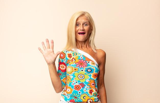 Frau mittleren alters, die sich glücklich, überrascht und fröhlich fühlt, mit positiver einstellung lächelt und eine lösung oder idee verwirklicht