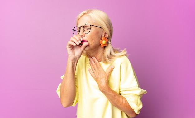 Frau mittleren alters, die sich mit halsschmerzen und grippesymptomen krank fühlt und mit bedecktem mund hustet