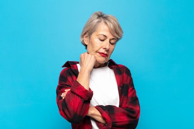 Frau mittleren alters, die sich nach einer ermüdenden, langweiligen und langweiligen aufgabe gelangweilt, frustriert und schläfrig fühlt und das gesicht mit der hand hält