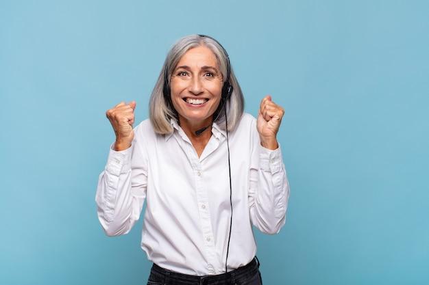 Frau mittleren alters, die sich schockiert, aufgeregt und glücklich fühlt und isoliert lacht