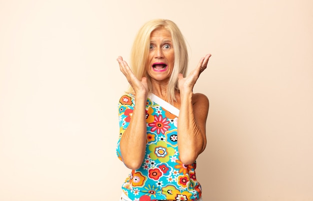 Frau mittleren alters, die sich schockiert und aufgeregt fühlt und isoliert lacht