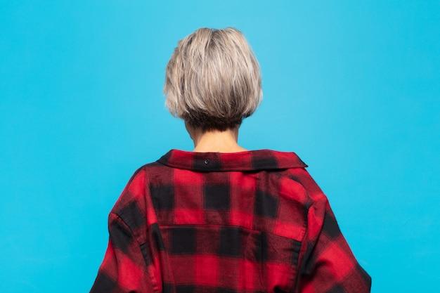 Frau mittleren alters, die sich verwirrt oder voll fühlt oder zweifel und fragen hat und sich wundert, mit den händen auf den hüften, rückansicht