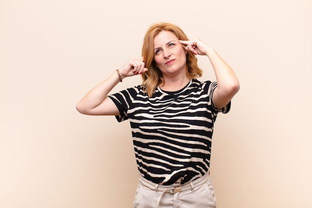 Frau mittleren alters, die sich verwirrt oder zweifelnd fühlt, sich auf eine idee konzentriert, hart nachdenkt und versucht, platz auf der seite zu kopieren