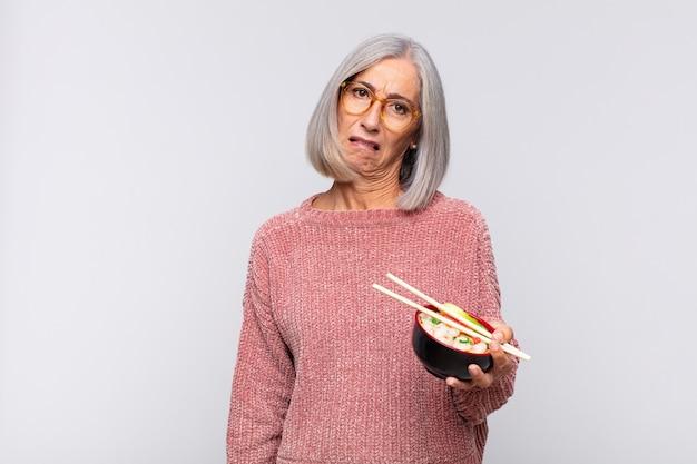 Frau mittleren alters, die sich verwirrt und verwirrt fühlt, mit einem dummen, fassungslosen ausdruck, der etwas unerwartetes asiatisches nahrungsmittelkonzept betrachtet