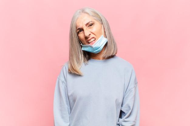 Frau mittleren alters, die sich verwirrt und verwirrt fühlt, mit einem dummen, fassungslosen ausdruck, der etwas unerwartetes betrachtet