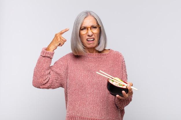 Frau mittleren alters, die sich verwirrt und verwirrt fühlt und zeigt, dass sie verrückt, verrückt oder verrückt nach asiatischem essen sind