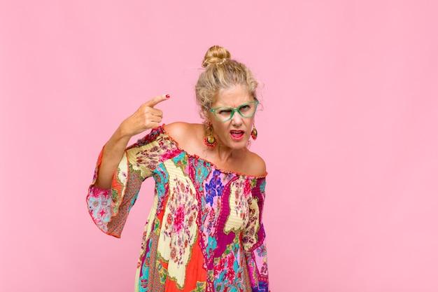 Frau mittleren alters, die sich verwirrt und verwirrt fühlt und zeigt, dass sie verrückt, verrückt oder verrückt sind