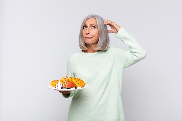 Frau mittleren alters, die sich verwirrt und verwirrt fühlt