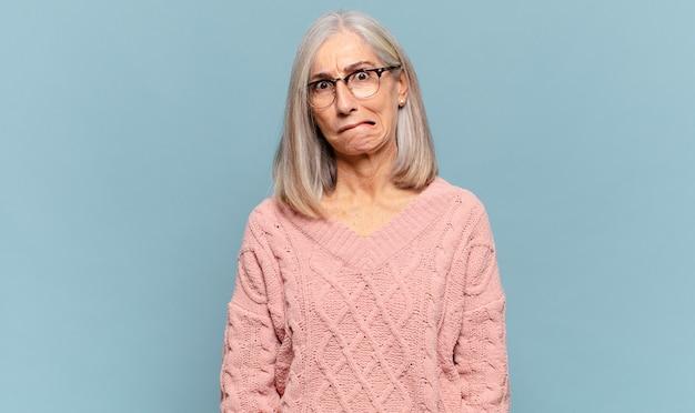 Frau mittleren alters, die sich verwirrt und zweifelhaft fühlt, sich wundert oder versucht, eine entscheidung zu treffen oder zu treffen