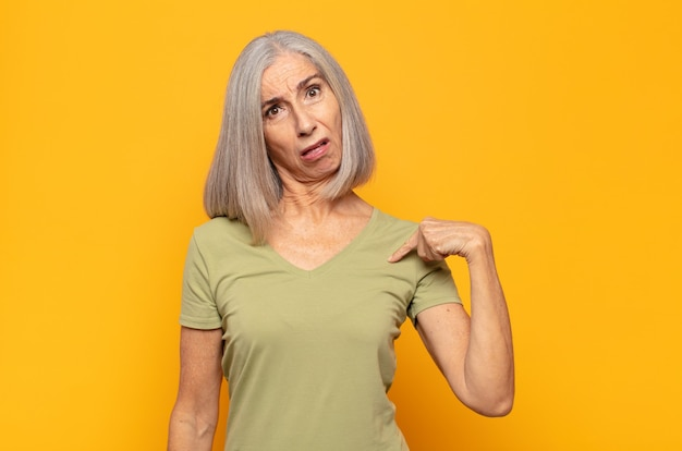 Frau mittleren alters, die sich verwirrt, verwirrt und unsicher fühlt, auf selbstwunder zeigt und fragt, wer, ich?