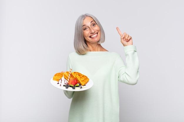 Frau mittleren alters, die sich wie ein glückliches und aufgeregtes genie fühlt, nachdem sie eine idee verwirklicht hat und fröhlich den finger hebt, eureka!. frühstückskonzept