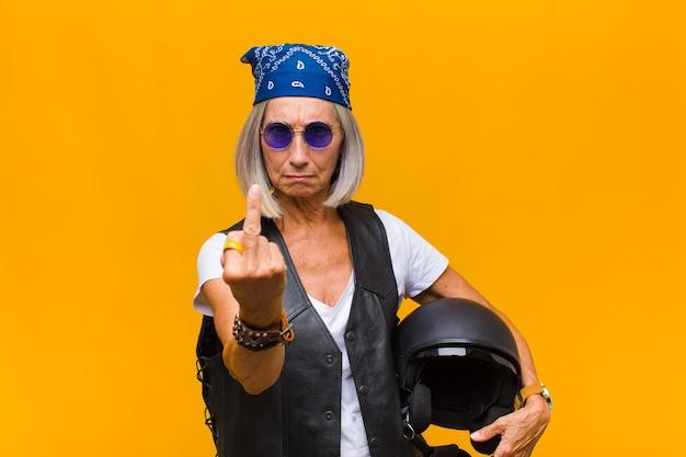 Frau mittleren alters, die sich wütend, verärgert, rebellisch und aggressiv fühlt, den mittelfinger umdreht und sich wehrt