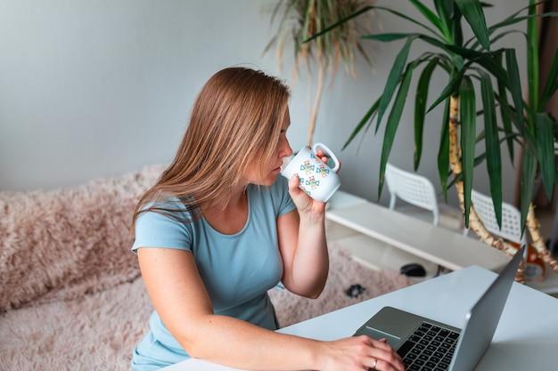 Frau mittleren alters, die tee trinkt, sitzt zu hause am tisch und arbeitet mit computer-laptop. arbeiten sie von zu hause aus und bleiben sie während des coronavirus-pandemie-konzepts zu hause