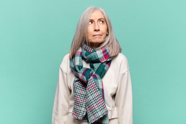 Frau mittleren alters, die traurig, verärgert oder wütend ist und mit einer negativen einstellung zur seite schaut und die stirn runzelt