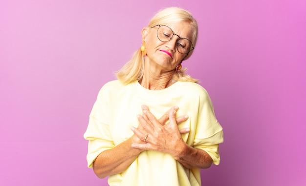 Frau mittleren alters, die traurig, verletzt und untröstlich aussieht, beide hände nah am herzen hält, weint und sich deprimiert fühlt