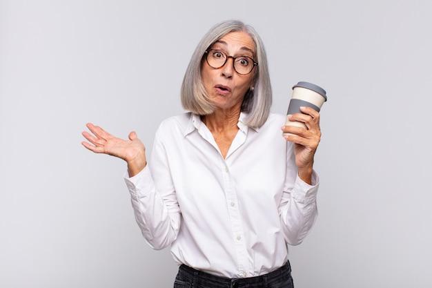 Frau mittleren alters, die überrascht und schockiert aussieht, mit gesenktem kiefer, der einen gegenstand mit einer offenen hand auf dem seitenkaffeekonzept hält