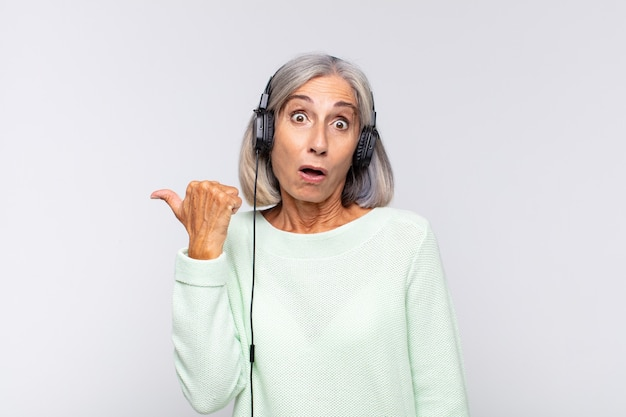 Frau mittleren alters, die ungläubig erstaunt aussieht und zeigt