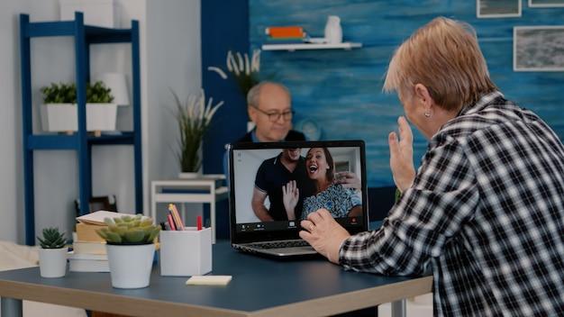 Frau mittleren alters, die videokonferenz mit kindern spricht, die auf laptop senior alte fernmutter...