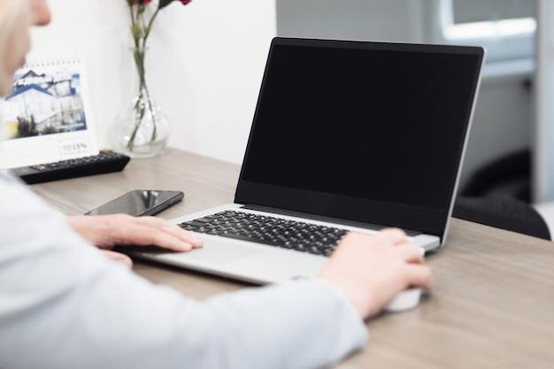 Frau mittleren alters, die von zu hause aus am laptop arbeitet, schließen die hände