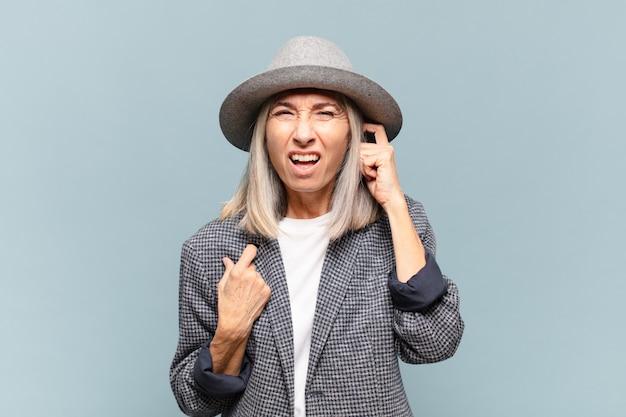 Frau mittleren alters, die wütend, gestresst und genervt aussieht und beide ohren mit einem ohrenbetäubenden geräusch, geräusch oder lauter musik bedeckt