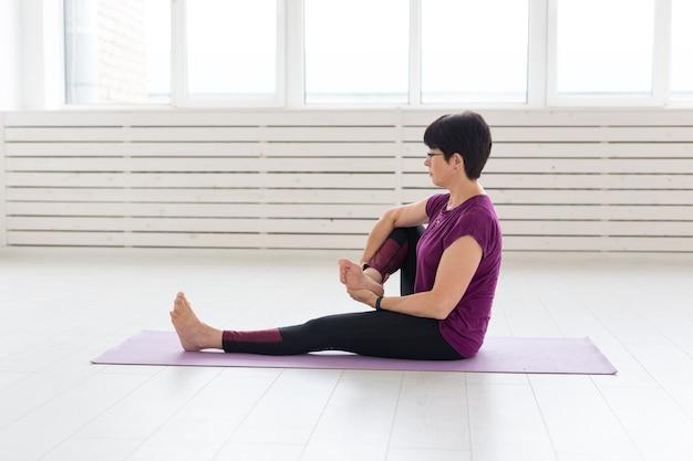 Frau mittleren alters, die yoga macht
