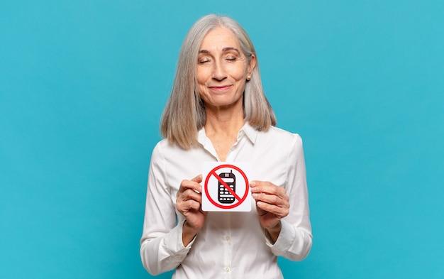 Frau mittleren alters, die zeichen hält, verbotene telefone. kein telefon verboten