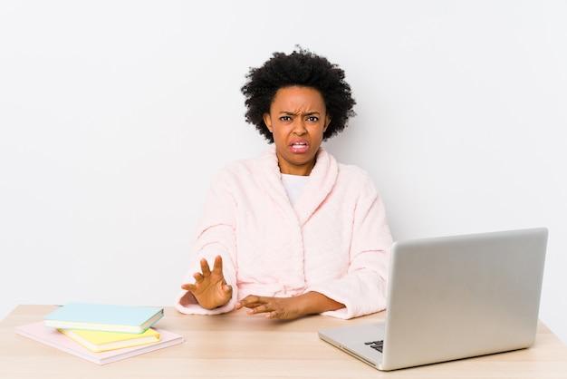 Frau mittleren alters, die zu hause arbeitet und jemanden ablehnt, der eine geste des ekels zeigt