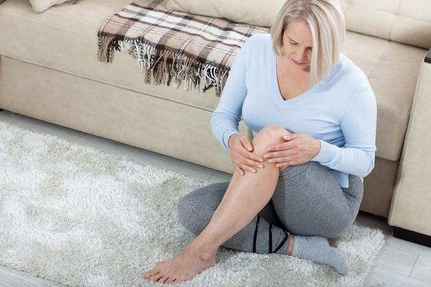 Frau mittleren alters, die zu hause unter beinschmerzen leidet.