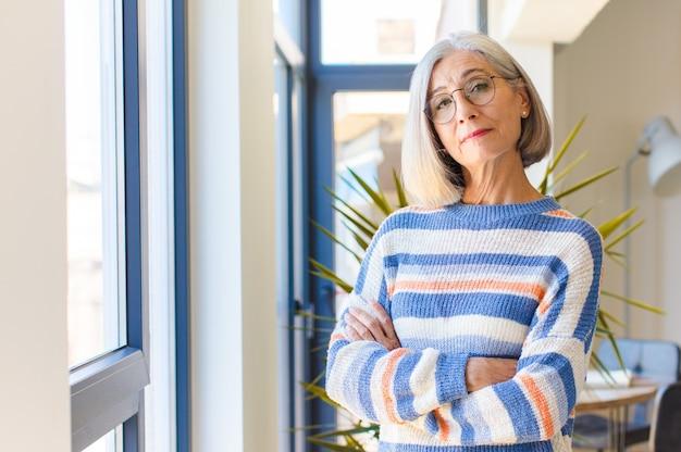 Frau mittleren alters, die zur kamera mit verschränkten armen und einem glücklichen, selbstbewussten, zufriedenen ausdruck, seitenansicht lächelt