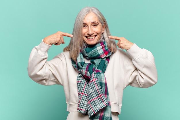 Frau mittleren alters, die zuversichtlich lächelt und auf ein breites lächeln zeigt, positive, entspannte, zufriedene haltung