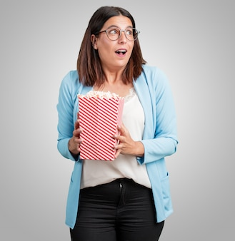 Frau mittleren alters glücklich und fasziniert, hält einen gestreiften popcorn-eimer, überrascht durch den neuen film, die augen offen und ausdruck der bewunderung
