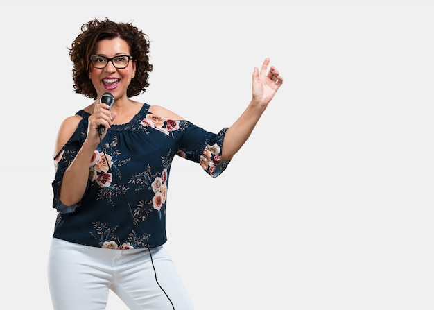 Frau mittleren alters glücklich und motiviert, ein lied mit einem mikrofon zu singen, ein ereignis zu präsentieren oder eine party zu feiern, genießen sie den moment