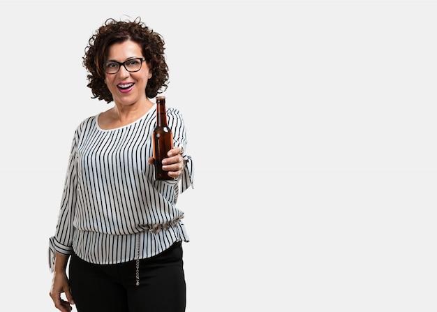 Frau mittleren alters glücklich und spaß, hält eine flasche bier, fühlt sich gut nach einem intensiven arbeitstag, bereit, ein fußballspiel im fernsehen zu sehen
