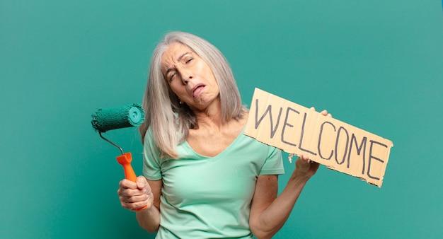 Frau mittleren alters graue haare mit einer farbrolle, die ihre wand schmückt
