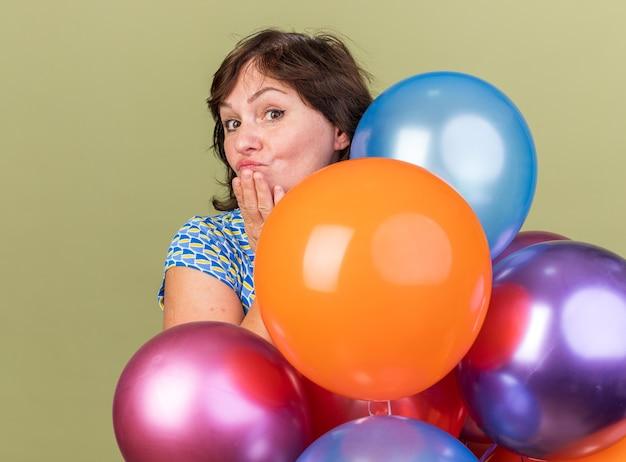 Frau mittleren alters haufen bunte luftballons mit lächeln auf glücklichem gesicht