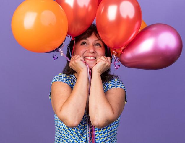 Frau mittleren alters haufen bunter luftballons, die mit einem lächeln auf einem glücklichen gesicht aufblicken