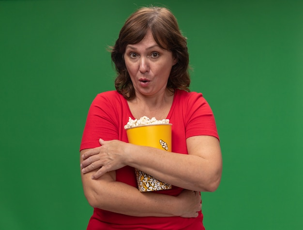 Frau mittleren alters im roten t-shirt, das eimer mit popcorn hält, überrascht, über grüner wand stehend