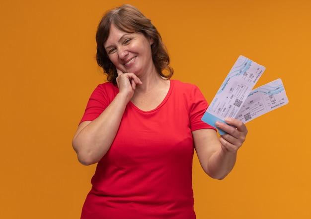 Frau mittleren alters im roten t-shirt, das flugscheine mit dem glücklichen gesicht lächelnd steht über orange wand hält