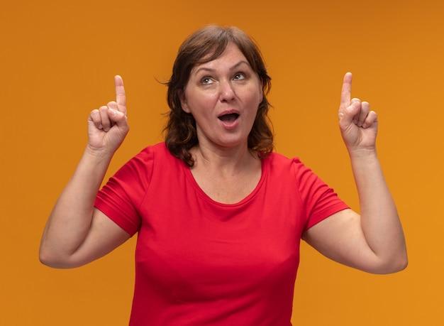 Frau mittleren alters im roten t-shirt, das lächelnd zeigt und mit zeigefingern oben steht über orange wand steht