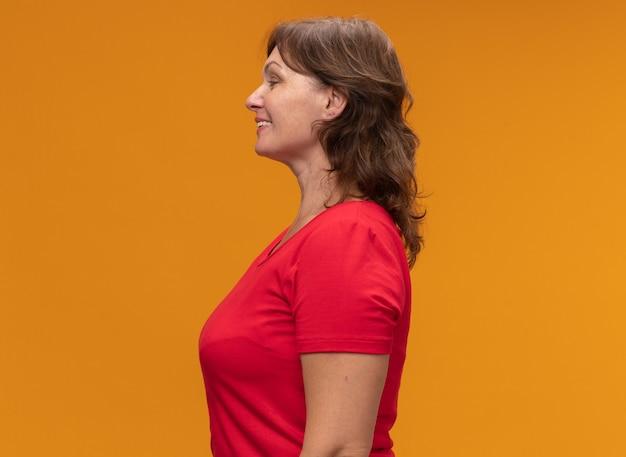 Frau mittleren alters im roten t-shirt, das seitlich mit lächeln auf gesicht über orange wand steht