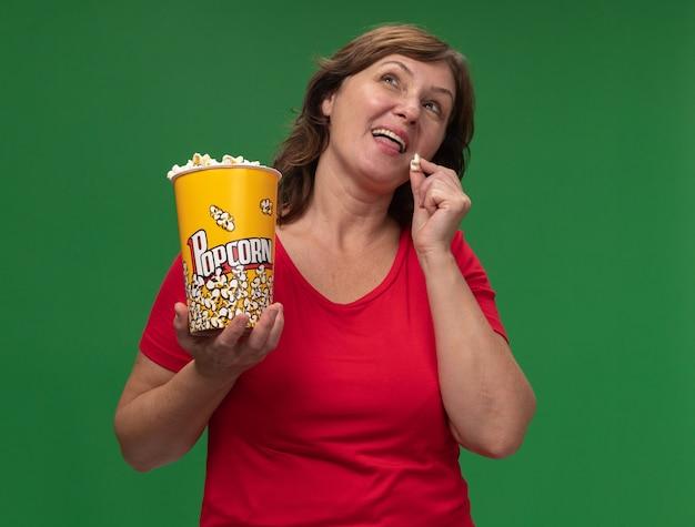 Frau mittleren alters im roten t-shirt, der eimer mit popcorn glücklich und positiv lächelnd steht über grüner wand hält