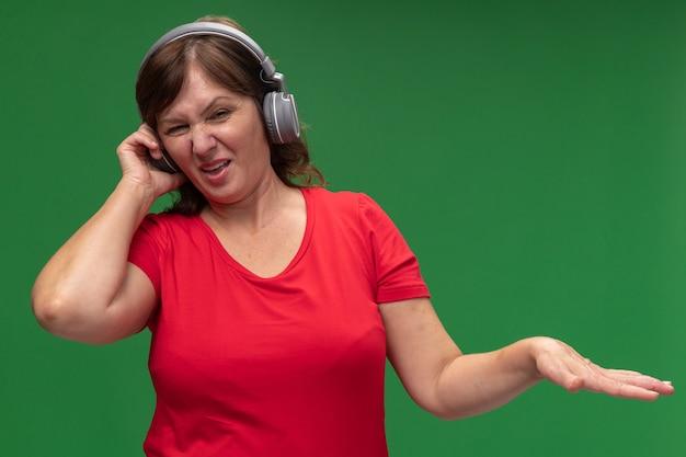 Frau mittleren alters im roten t-shirt mit kopfhörern mit angewidertem ausdruck, der arm erhöht, der über grüner wand steht