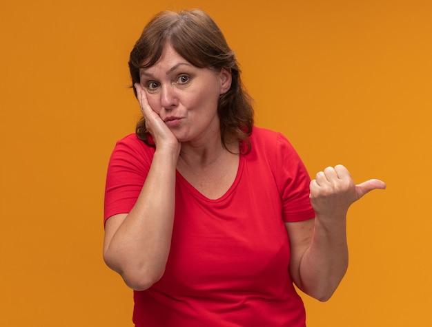 Frau mittleren alters im roten t-shirt zeigte erstaunt mit dem daumen zur seite stehend über der orangefarbenen wand