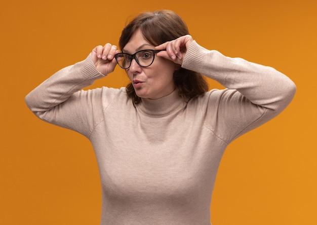 Frau mittleren alters in beigem rollkragenpullover, der eine brille trägt, die dicht über der orangefarbenen wand steht