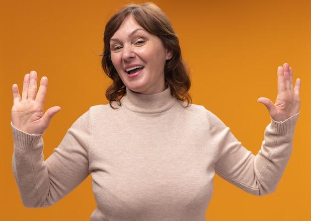 Frau mittleren alters in beigem rollkragenpullover glücklich und fröhlich lächelnd, die palmen in der übergabe stehend, die über orange wand steht