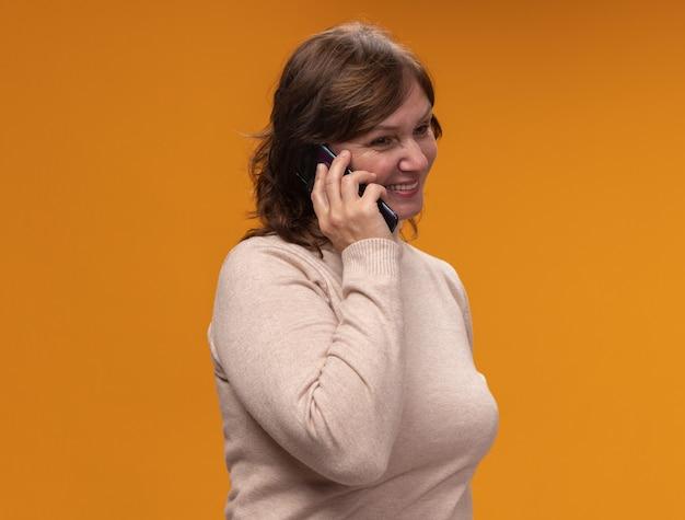 Frau mittleren alters in beigem rollkragenpullover glücklich und positiv lächelnd, während auf mobiltelefon steht über orange wand
