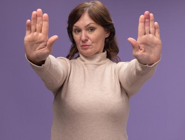 Frau mittleren alters in beigem rollkragenpullover mit ernstem gesicht, das stoppgeste mit den händen macht, die über lila wand stehen